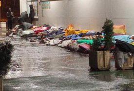 HUMANITARNA KATASTROFA NA POMOLU Migranti u Tuzli spavaju na kiši, pored njih teku potoci vode