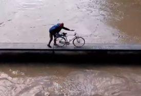 OPASNO I RIZIČNO Čovjek zaštitnim zidom prevezao bicklo pokraj nabujale rijeke (VIDEO)